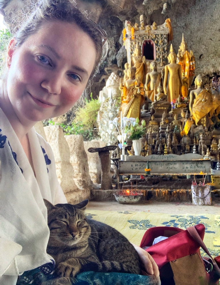 Solo female traveler and a cat in a Laos cave temple
