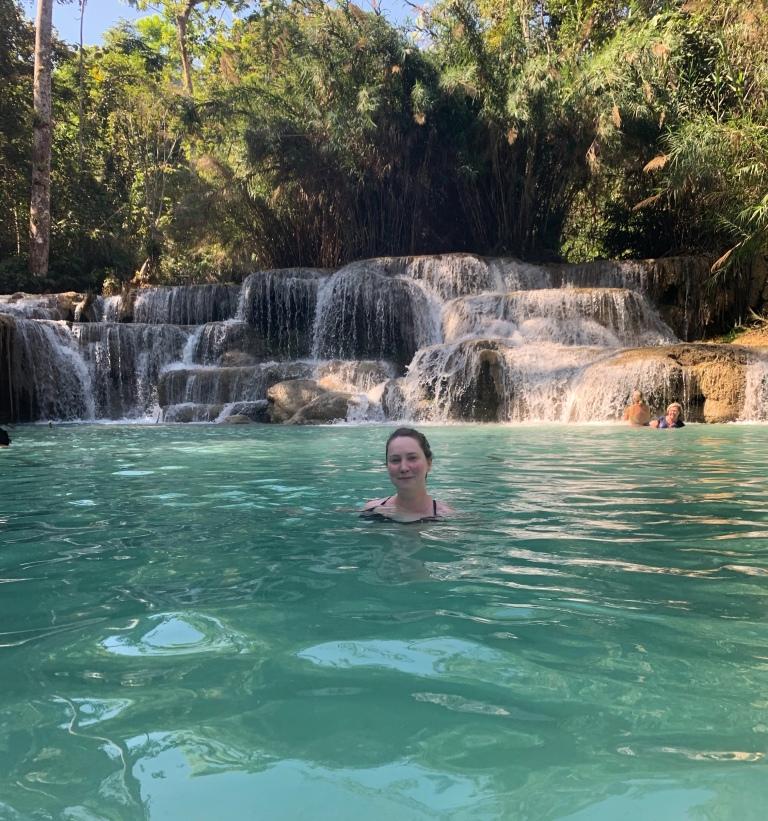Solo female traveler swimming in Kuang Si Falls in Luang Prabang Laos