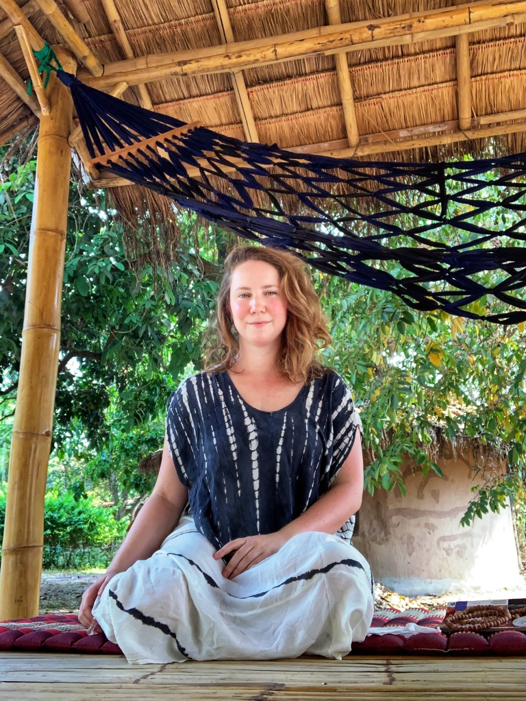 A solo female traveler meditating at a yoga retreat in Chiang Mai Thailand