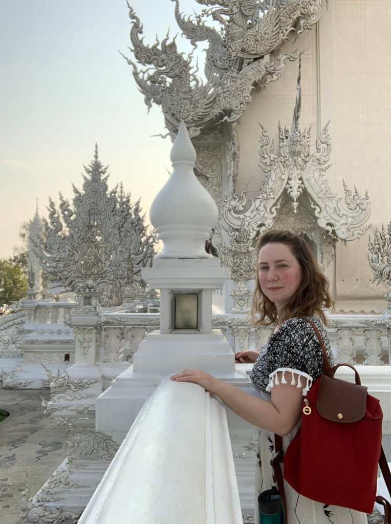 A woman traveling alone at the White Temple in Chiang Rai Thailand